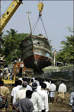 A crane removes a fishing trawler from a road at Nagapattinam port, some 217 miles south of Madras.