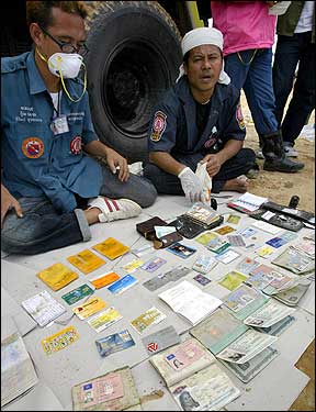 Thai rescue workers display the passports and IDs of different Western tourists after collecting them from the debris in Khao Lak.