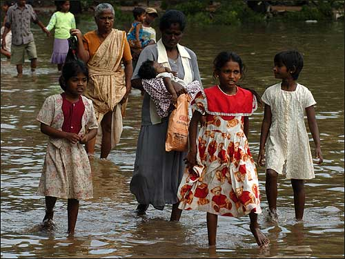 Tsunami survivors walked in the streets flooded by heavy rains in the village of Ariampadi.
