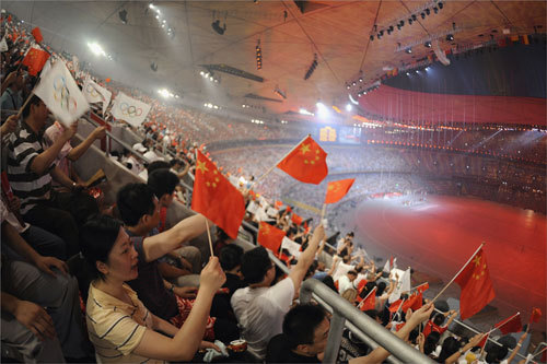 Spectators who were lucky enough to score tickets to watch the opening ceremonies from inside the 'Bird's Nest' waved national flags and Olympic flags as they witnessed elaborate performances.