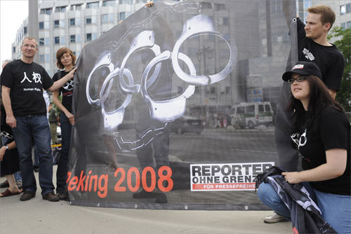 Participants of'Reporters without Borders' held a banner depicting the Olympic rings shaped as handcuffs as they protested in front of the Chinese embassy in Berlin.