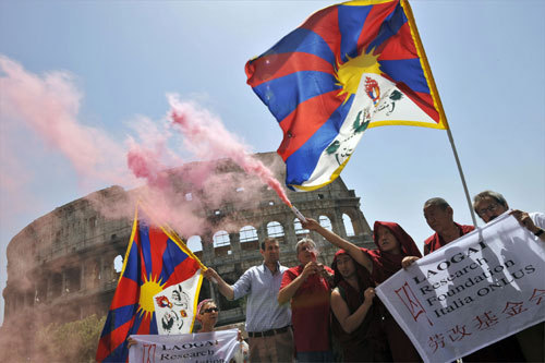 About a dozen pro-Tibet monks and activists displayed Tibetan flags as they demonstrated in front of the ancient Colosseum in Rome.