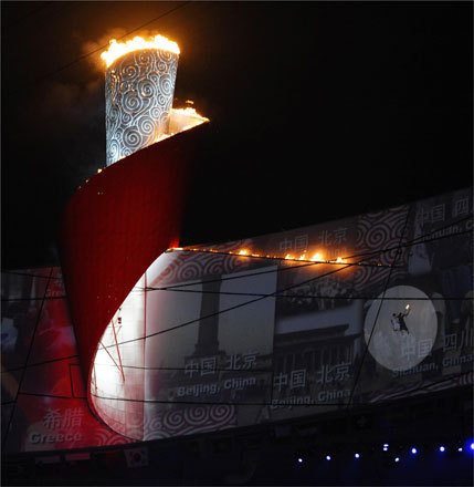 The Olympic flame burned as Ning was lowered back down to the ground after flying across the top of the stadium in the last run high-flying run of the torch relay.