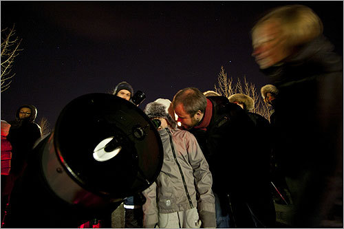 The crowd of about 30 people in the Reykjavik parking lot braved the bitter cold to gather around a telescope set up by the Amateur Astronomical Society to observe the eclipse.