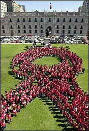 1,000 volunteers dressed in red stand forming the bow symbol of the campaign against AIDS