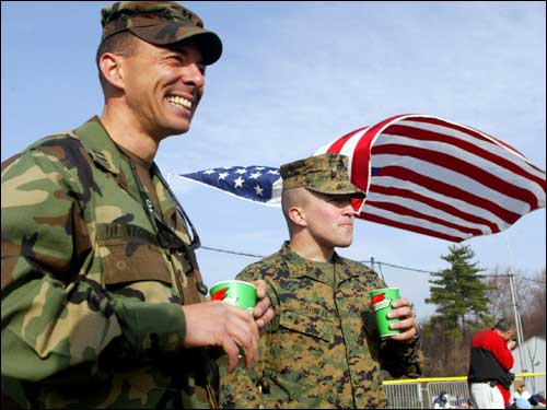 US Army Capt. Jose DeVarona (left) smiles and shares a beverage with VMI cadet Ross Garnett prior to the start of the Boston Marathon. DeVarona and Garnett are two of six soldiers that will be running in support of Americans killed in the Iraqi conflict.