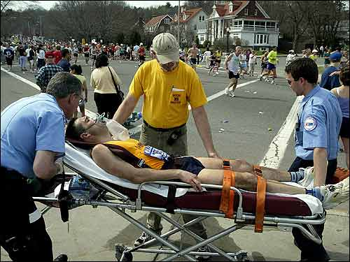 More than just an annoyance, the heat could also be dangerous. Here Manuel Tapia, of Oxford, Mich., who collapsed after mile 19 at Heartbreak Hill, is attended by paramedics.