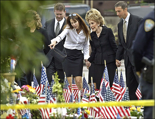Nancy Reagan, her daughter, Patti Davis, and son, Ronald Prescott Reagan, look over hundreds of souvenirs and flags left at the funeral home in Santa Monica, Calif., where Ronald Reagan's body was prepared for burial.