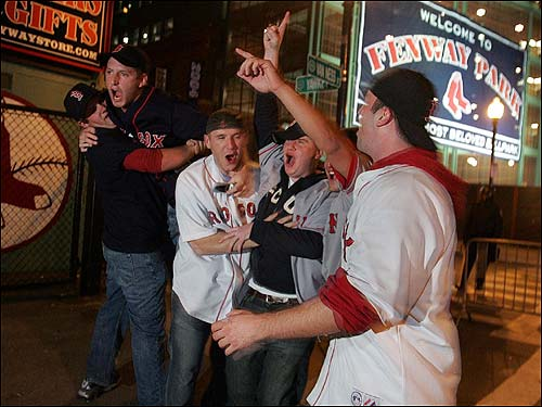 A group of excited fans gather together behind Fenway Park.