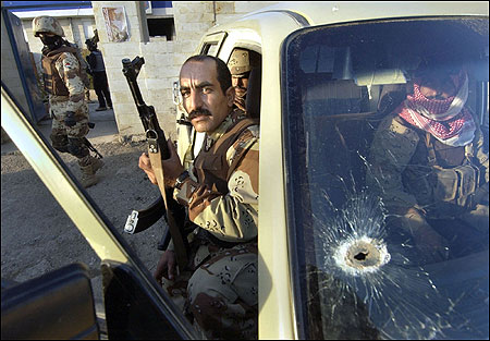 Iraqi National Guard soldiers left a police station last Thursday to recover the bodies of two men found dead in Mosul.