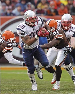 Patriots running back Corey Dillon bursts past Cleveland defenders Barry Gardner, left, and Chaun Thompson on a 21-yard run in the first quarter.