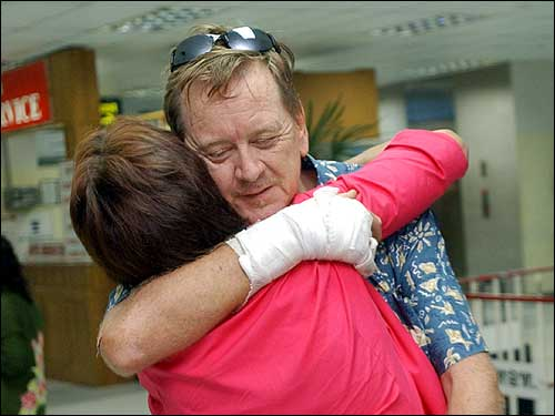 Ron Jory of Toronto, Canada, hugs Jill Thomas of New Zealand, following her arrival at Phuket International Airport. Thomas' sister died Sunday in the tsunami.