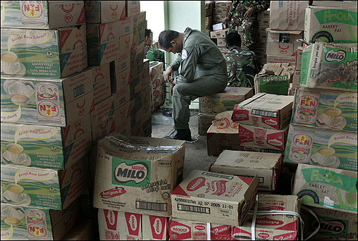 An Air Force crewman tries to catch a much-needed rest amidst boxes of relief supplies in Banda Aceh.