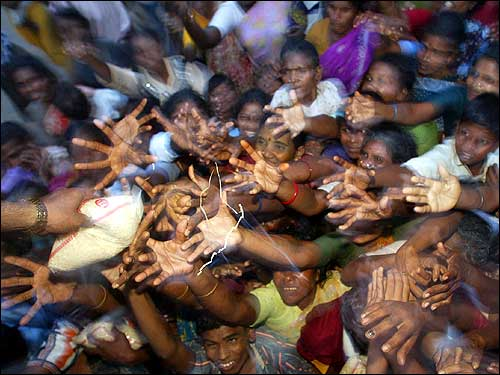 Tsunami victims at a relief camp reach for rice packets being distributed in Nagappattinam, in the southern Indian state of Tamil Nadu