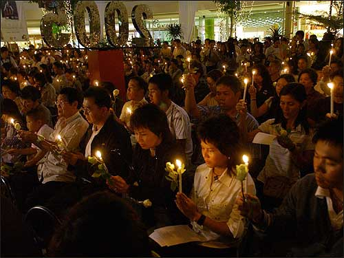 Thais and foreigners pray for the tsunami victims during a candlelight vigil outside a shopping mall in Phuket province.