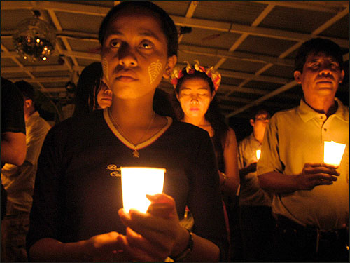 Participants hold candles as they pray for the victims during the New Year's Eve vigil in Dili.