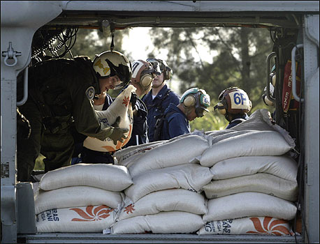 US Navy personnel from the aircraft carrier USS Abraham Lincoln load food, water, and other supplies onto a US Navy Seahawk helicopter at Banda Aceh airport today.