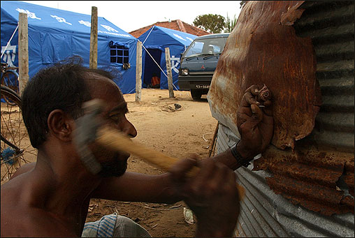 A tsunami victim repairs a makeshift dwelling today at a camp for victims in the eastern coastal town of Batticaloa.