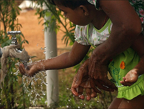A young girl washes her hands with her mother in a camp for tsunami victims in Batticaloa.