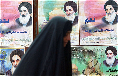 An Iraqi woman walks past election posters containing the portrait of the Grand Ayatollah Ali al-Sistani in Baghdad, earlier this week. The posters read, ''United Iraqi Alliance elections equal security and stability.''