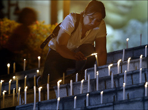 A Catholic devotee lit candles on the steps of a shrine near Manila after attending a special Mass for the pope's recovery.