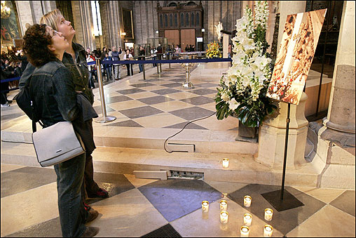 Visitors to Notre Dame Cathedral in Paris stood before a photograph of Pope John Paul II.