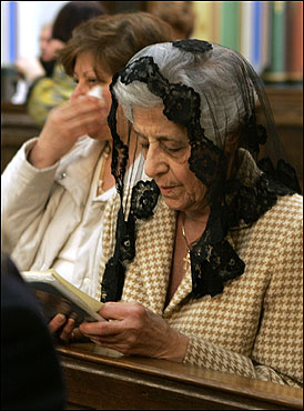 A woman in mourning prayed as another woman wiped her tears in a Roman Catholic church in Amsterdam.