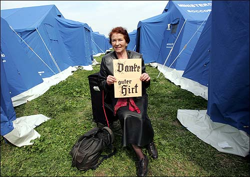 Woman holding up a sign between tents.
