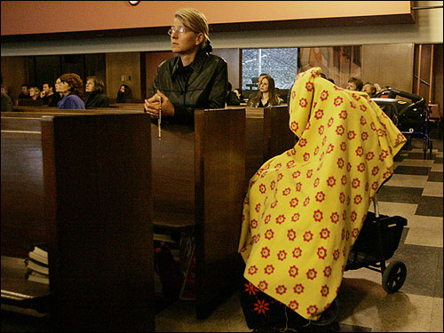 Anna Dabrowska-Dudek of La Canada, Calif. knelt and prayed as she watched a live television feed of Pope John Paul II's funeral from inside a Los Angeles church. To the right, a blanket covered her three-year-old daughter as she slept in her stroller.