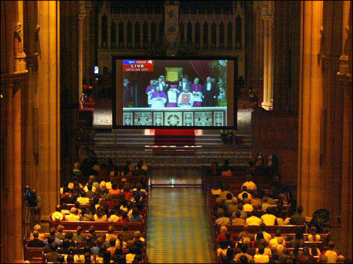Mourners in St. Mary's Cathedral in Sydney watched a large screen TV as the coffin of Pope John Paul II was carried to his funeral service. The cathedral had several large and small screen projections of the live telecast of the pope's funeral.
