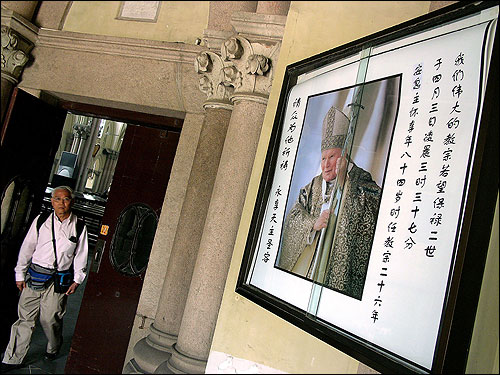 A visitor walked near a mourning sign for the late Pope John Paul II at a government-approved Catholic church in Shanghai. China said it would not send an envoy to the funeral because the Vatican maintains diplomatic relations with rival Taiwan, and complained about plans for Taiwanese President Chen Shui-bian to attend.
