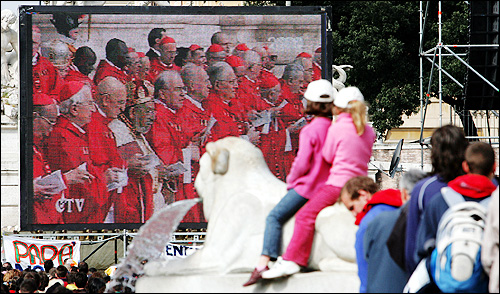 Two young girls sat on the statue of a lion in Piazza Del Popolo and watched the live broadcast of the pope's funeral on a giant video screen.