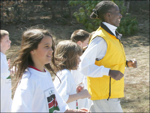 Ndereba runs with Elmwood Elementary School students in Hopkinton on Thursday.