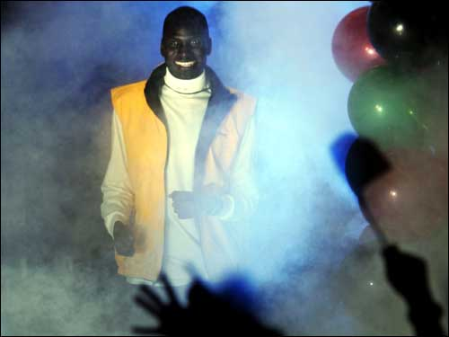Men's 2003 Boston Marathon champion Robert Cheruiyot comes through a cloud of smoke.