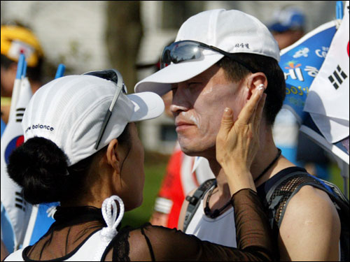 Runner Lee Sang Chul (right) got some help applying sunscreen from To Soon Yu (left) near the starting line. Both are from North Korea.