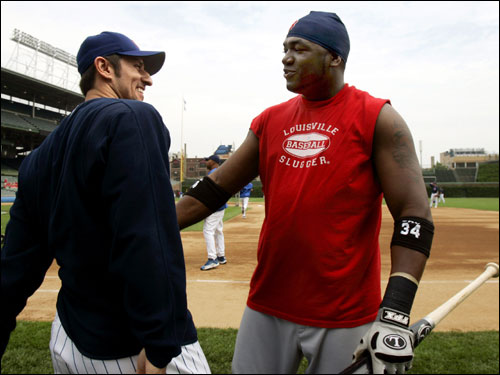 Nomar Garciaparra laughs with former teammate David Ortiz before the start of the first game of the Cubs-Red Sox weekend series.
