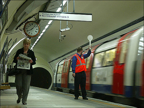 A female passenger read the morning paper as she walked along an empty platform at Kennington Station today.