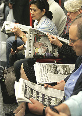 Commuters read the morning news as they traveled on the London subway's Central Line during morning rush hour today.