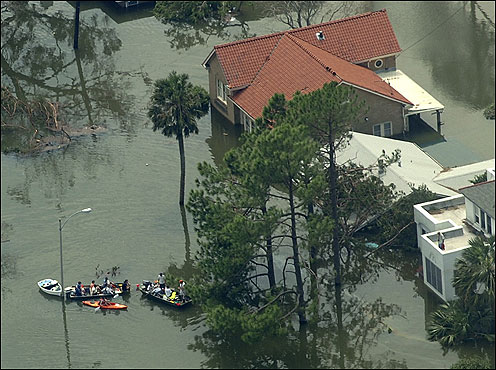 People negotiated neighborhood flooding in boats in Arabi, a suburb of New Orleans, yesterday.