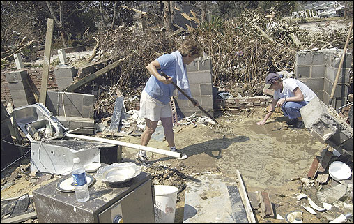 Melanie Moore (left) used a rake to check a puddle as she tried to salvage china where her dining room used to be, as her sister-in-law, Ann Reimer, helped in Pascagoula, Miss.
