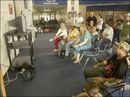 Evacuees gathered in front of a television to watch the news at the Red Cross shelter in Vancleave (Miss.) High School on Wednesday morning.