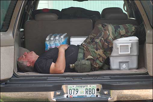 Mississippi Air National Guard Tech Sergeant Dave Bigham rested in the back of a sport utility vehicle after suffering from heat cramps passing out ice and bottled water at the Pike County Fairgrounds in McComb, Miss., Thursday.