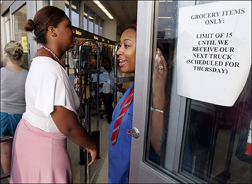 Jazmyn Smith (right) let Kendra Jaynes into a drug store to buy a maximum of 15 items in Hattiesburg, Miss., Thursday. Irregular shipments of goods has caused some stores to place a limit on how much each person can buy in the aftermath of Hurricane Katrina.