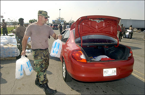 US Army National Guard Specialist Chris Fabris of Brundidge, Ala., loaded ice into the trunk of a car at an aid pickup point at Singing River Mall in Gautier, Miss., Friday.