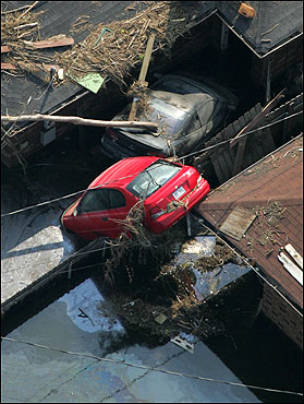 Cars that were tossed during the hurricane remain perched atop homes in St. Bernard Parish, La.