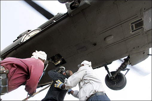 Donald Davis (left), Stacey Hodnett (center), and Willie Harris, all members of the US Corps of Engineers based in New Orleans, loaded a sand bag weighing nearly 7,000 pounds to the cargo hook on the belly of a Blackhawk helicopter. The sand bags will be used to fill holes where levees have breached.