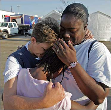 Salvation Army volunteers Nancy Hatcher (left) prayed with Vickie Sims (right) and her daughter, Frensha, as they arrived for another day of distributing aid to victims of Hurricane Katrina in Biloxi, Miss.