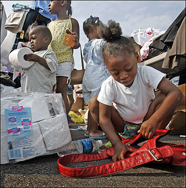 Robert Devone Cherry (left) played with toilet paper while Zytina Tucker, 5, examined a purse she found in a donation distribution area for victims of Hurricane Katriana in Gulfport, Miss.