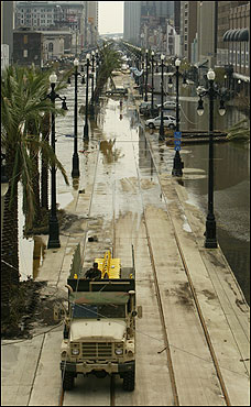A military vehicle moved along the streetcar right-of-way in the middle of Canal Street in downtown New Orleans.