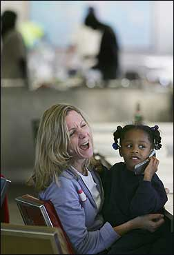 Ann Reale, head of the Massachusetts Early Education and Care Council, laughed as she listened to Hurricane Katrina refugee Keyontay Dimes, 6, of New Orleans, talk on a cellular phone Sunday at Camp Edwards.